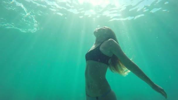 Zpomalený pohyb žena plavání pod vodou směrem k povrchu s krásnou sluneční erupce v pomalém pohybu