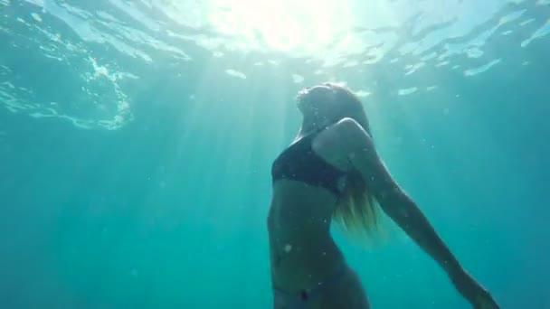 Žena, plavání pod vodou směrem k povrchu s krásnou sluneční erupce v pomalém pohybu
