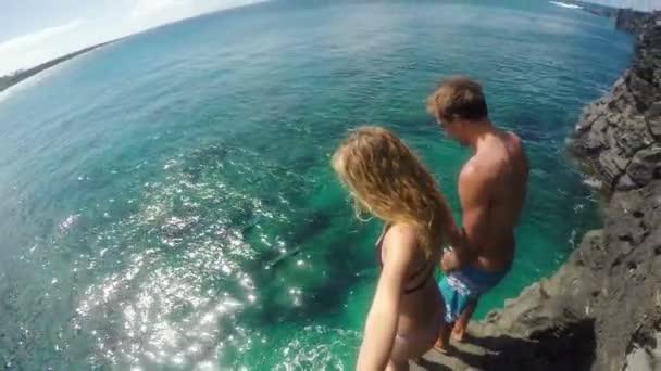 GoPro Pov zpomalené mladý atraktivní pár skokem z útesu do moře. Zábava džungle. Selfie hůl