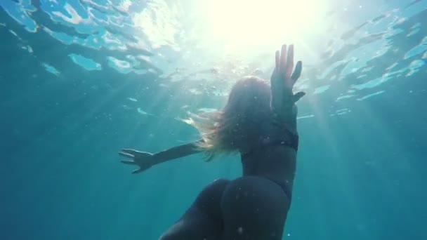 Žena v plavkách, plavání pod vodou směrem k povrchu jako mořská panna s krásnou sluneční erupce v pomalém pohybu