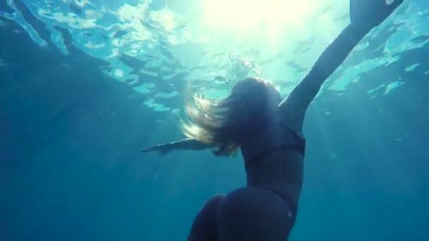 Frau im Bikini Schwimmen unter Wasser in Richtung Oberfläche wie eine Meerjungfrau mit schönen Sonne Flares in Zeitlupe