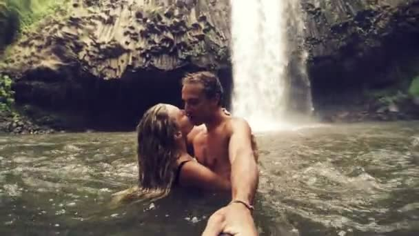 Cute Young Couple Holding Kissing in front of Waterfall with POV Selfie Stick. Happy cheerful young multicultural couple on travel. Slow Motion