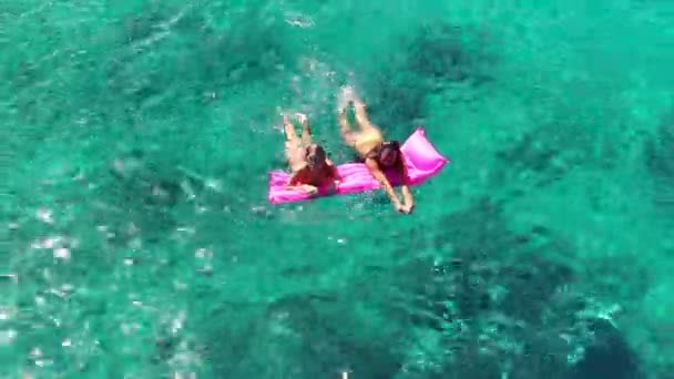 Beautiful Young Women In Bikinis Floating on Pink Inflatable Raft in Crystal Ocean in Hawaii.