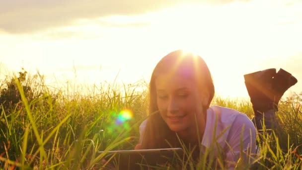 Young Woman Using Tablet Computer Touchscreen. Beautiful Sunset Light Outdoors in Nature.