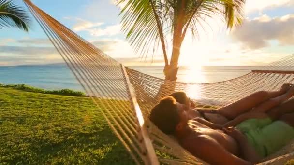 Romantika a kellemes naplementekor trópusi függőágyban relaxál