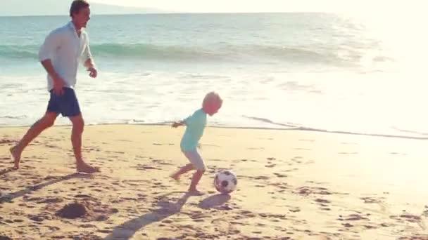 Vater und Sohn spielen gemeinsam Fußball am Strand bei Sonnenuntergang.