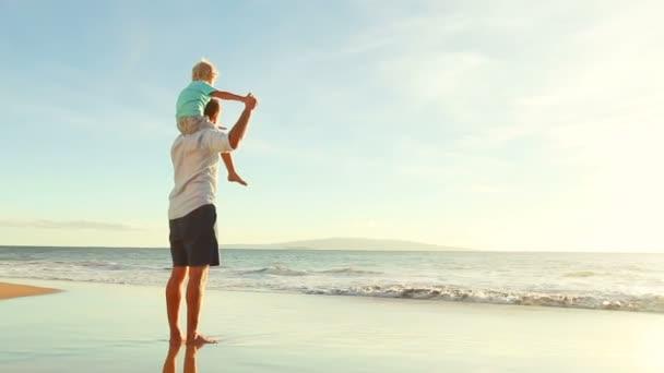 Apa és fia együtt játszik a tengerparton naplementekor.
