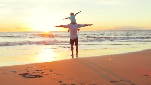 Otec a syn hrát letadlo zbraněmi vychováváni společně na pláži při západu slunce