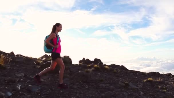 Hiker with Backpack Hiking on top of a mountain with sun flares. Young Healthy Woman Adventure in Nature.