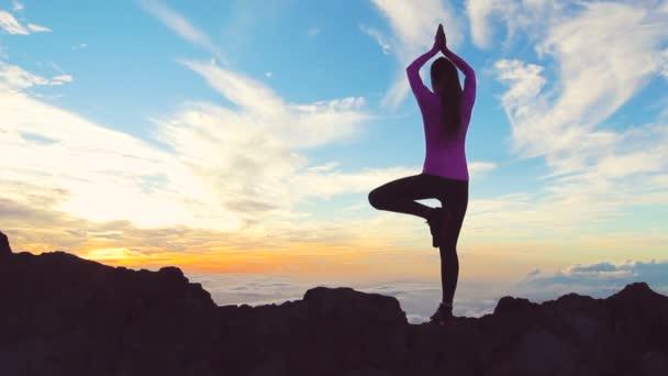 junge Frau in Yoga-Pose auf dem Gipfel des Berges. Die Spitze erreicht.