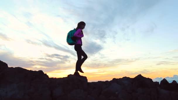 Der Wanderer wandert bei Sonnenuntergang am schmalen Gipfelgrat entlang. Die Spitze erreicht.