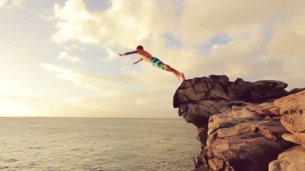 Cliff skákání při západu slunce. Aktivní odpočinek v létě útesu venkovní životní styl