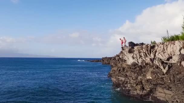 Klippen aus der Luft, die ins blaue Meer springen. junger Mann springt in Zeitlupe von Klippe Extremsport im Sommer.