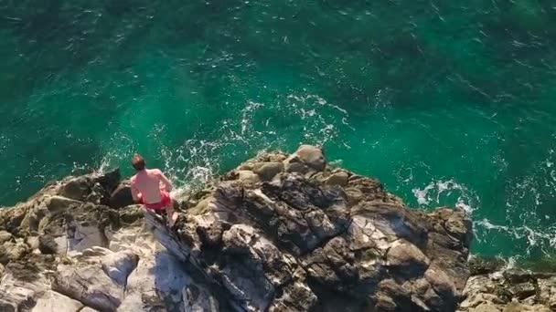 Klippen aus der Luft, die ins blaue Meer springen. Sommer Action Sport Lifestyle. Junger Mann springt in Zeitlupe von Klippe.