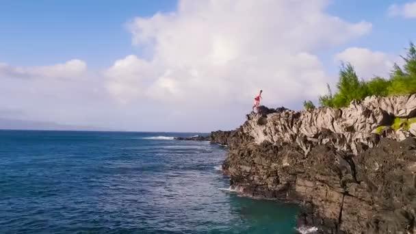 Extremer Rückwärtssalto beim Klippenspringen. Klippe aus der Luft springt ins blaue Meer.