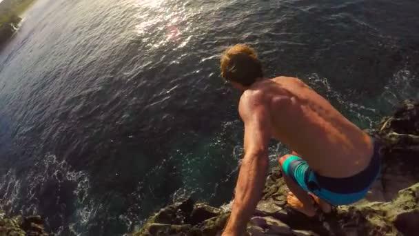 POV zpomalené Gopro Selfie Stick útesu. Sportovní mladý muž skočil z útesu do oceánu