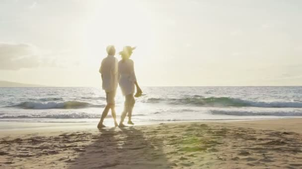 Sunset procházka na luxusní pláži. Starší dvojice drží ruce a procházky dolů po pláži při západu slunce jak se mojí nohy
