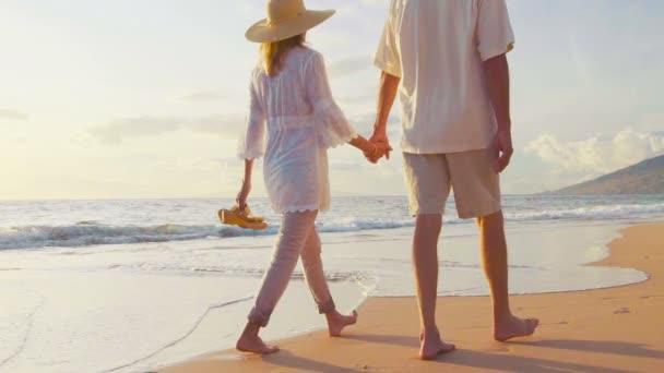Cesta po západu slunce na tropické pláži. Starší dvojice drží ruce a procházky dolů po pláži při západu slunce jak se mojí nohy