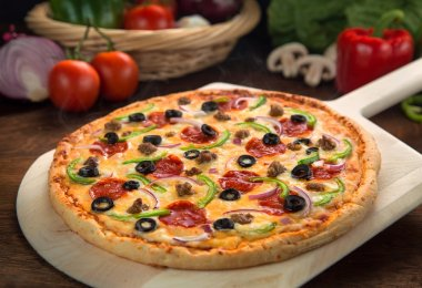 Entire supreme pizza baked cooked fresh and hot from oven served on wood surface