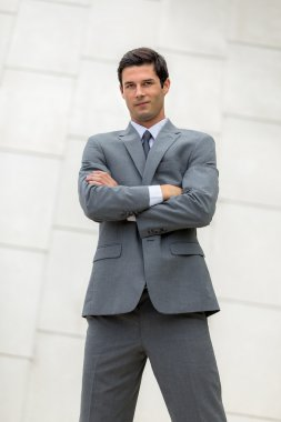 Vertical shot of confident business man young adult folded arms in powerful standing pose