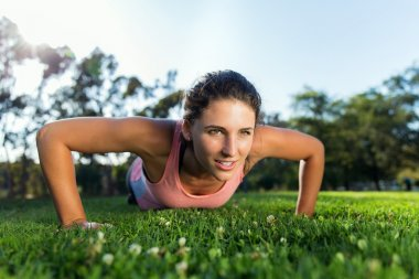 Pretty woman intense workout outdoors in park strong muscles