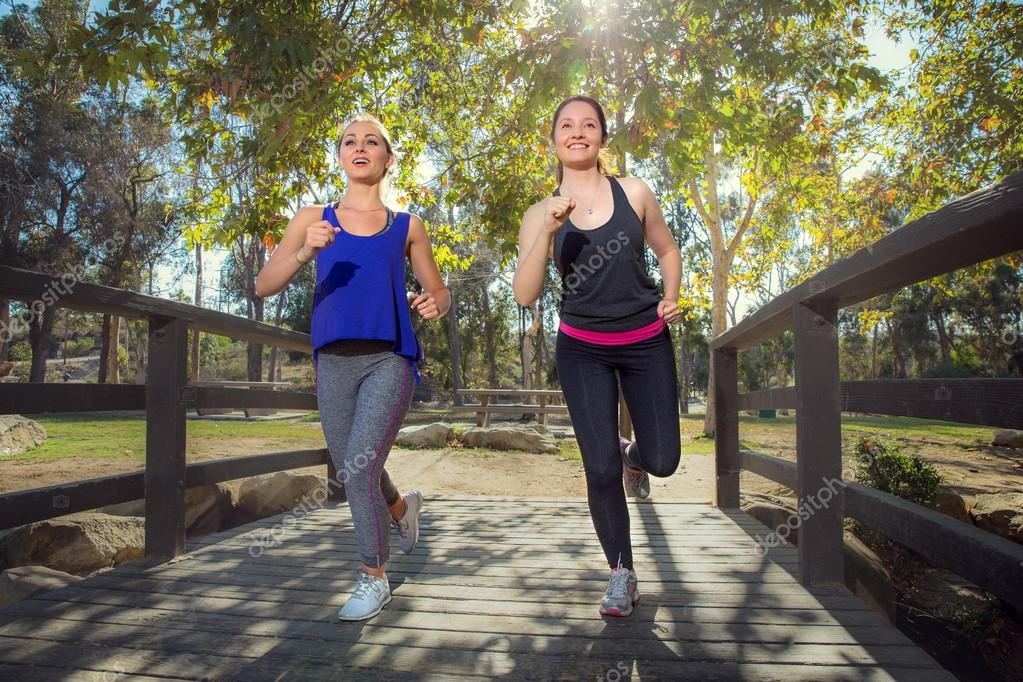 Two female joggers running in nature happy and fit in shape great exercise
