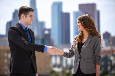 Male and Female business couple group leaders shaking hands downtown city