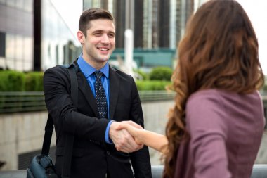 Handshake between two business people attractive smiling downtown buildings city