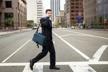 Businessman crossing the street crosswalk on way to work fast paced with cellphone
