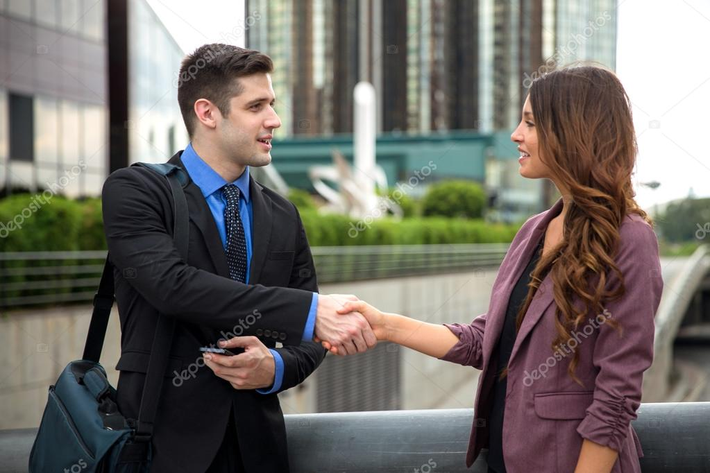 Two businesspeople shake hands traveling meeting greeting ...