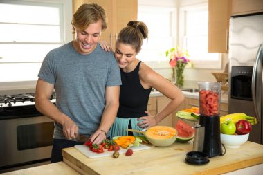 Attractive people in a kitchen making healthy low calorie smoothie lunch breakfast with fruits and veggies