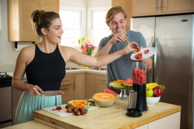 Couple lovers man and woman make a smoothie with fresh fruits ingredients in a blender