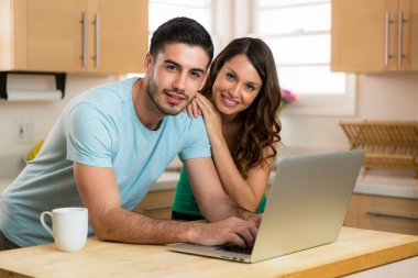 Husband and wife couple sharing a computer laptop social network laughing smiling searching for funny content with coffee