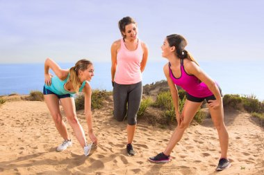 Friends women cute pretty casual conversation athletes stretching in exercise class outdoors before jog and hike on trail path