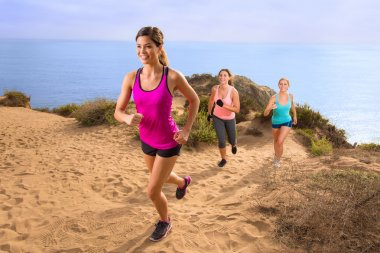 Exercise team fitness group jogging running hiking up hill trail path in nature