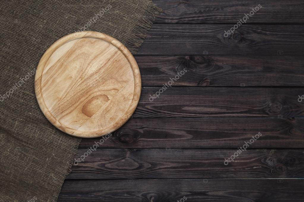 Tablero de corte redondo en mesa de madera oscura foto for Tablero redondo para mesa