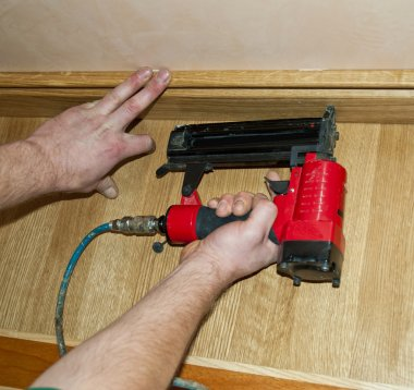 Worker pound in a nail to batten for wooden oak floor, floating