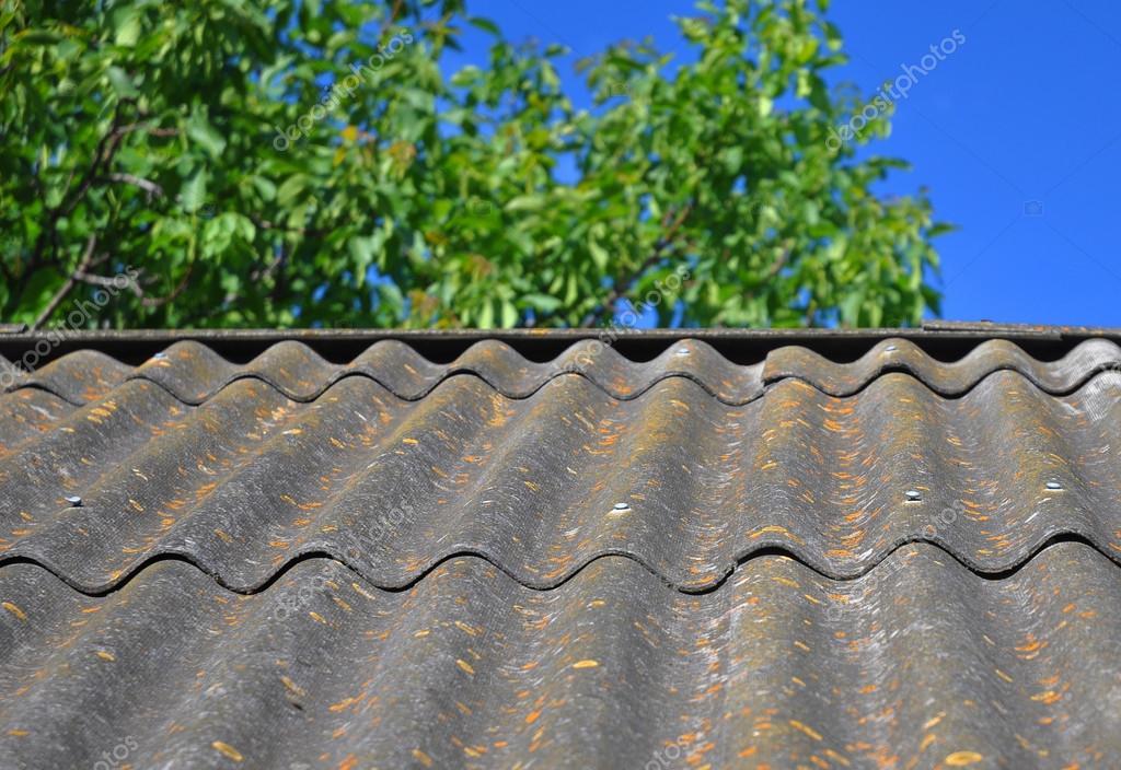 Cielo blu sopra il vecchio tetto di amianto pericoloso piastrelle in