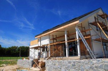 New frame house under construction, facade  against blue sky.