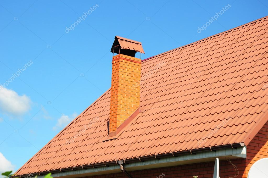 Faded red metal roof tile, rain gutter and chimney against blue sky.