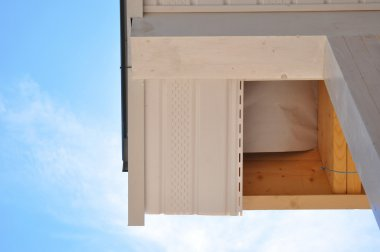 Corner of house with eaves against summer background. Install soffits. Roofing works.