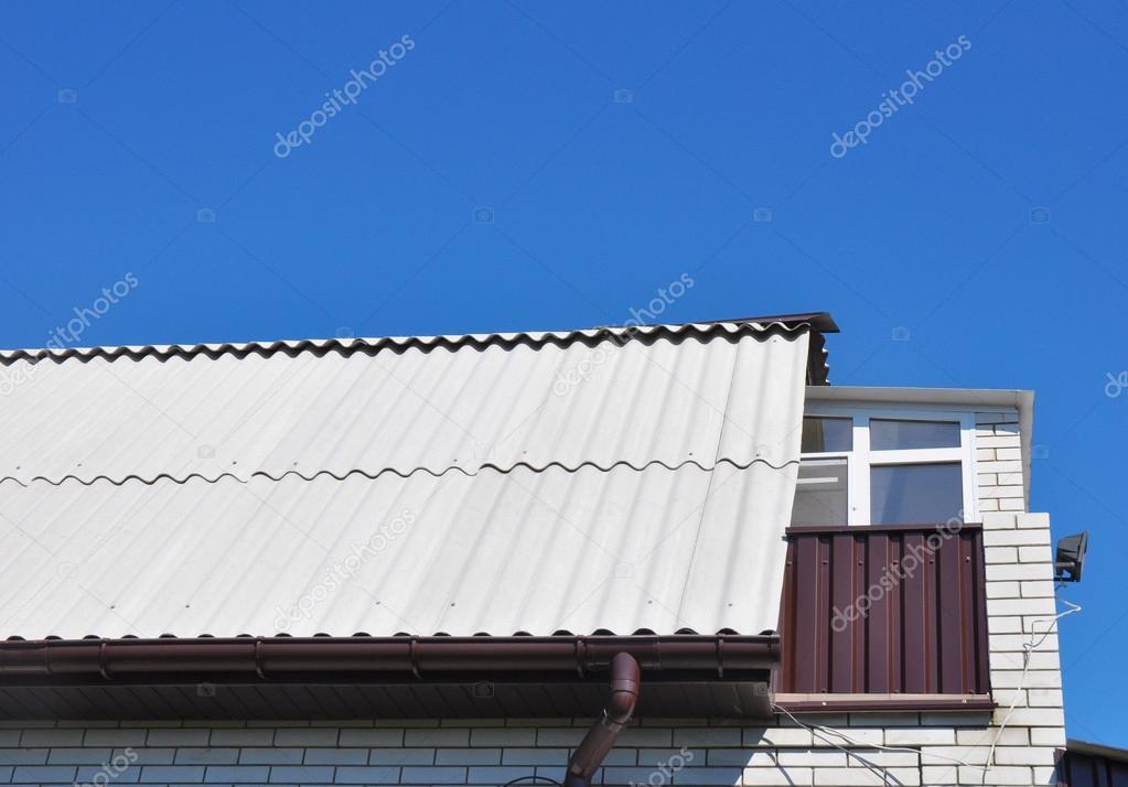 finestra sul tetto cielo blu sopra le tegole del tetto nuovo amianto