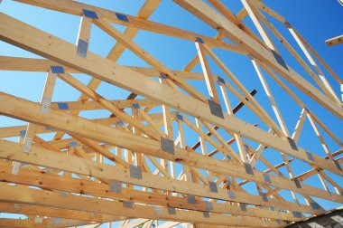 New residential construction home framing against a blue sky. Roofing construction.