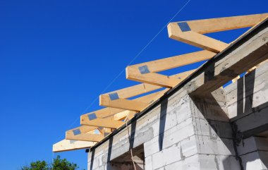Installation of wooden beams at construction the roof truss system of the house. Roofing.
