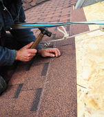 Roofer installs bitumen roof shingles with hammer and nails - cl