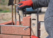 Fotografia Operaio del muratore linstallazione di blocchi rossi e calafataggio esterno muro di mattoni muratura giunti con coltello a spatola stucco e fissaggio con livella allaperto