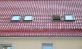 Červená kovová taškovou střechou s nové vikýře, střešní okna, světlíky, Rain Gutter systém a střešní ochranu před sněhem desky