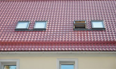 Red Metal Tiled Roof with New Dormers, Roof Windows, Skylights, Rain Gutter System and Roof Protection from Snow Board
