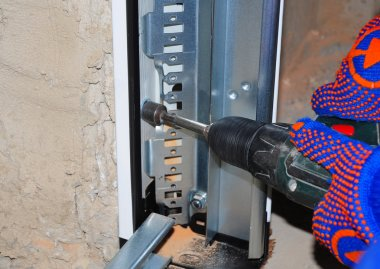 Garage Door Panel Installation. Man Using Drill to Attach Door Plastic and Metal Profile  Panel to Wall.