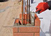 Fotografia Primo piano di un muratore operaio installazione rosso blocchi e calafataggio mattoni muratura giunti parete esterna con spatola stucco coltello allaperto